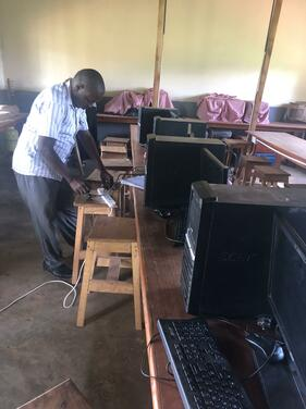 Mr. Katumba making connections in Kalere SS computer lab